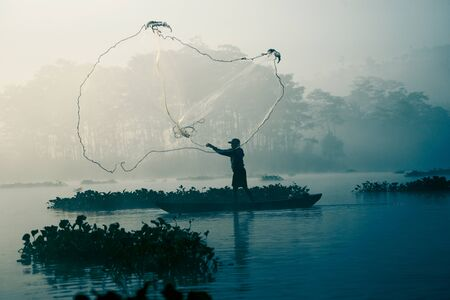riverbank: Fisherman casting out his fishing net in the river by throwing it high up into the air early in the morning to catch blue colored fish with his little fishing boat.