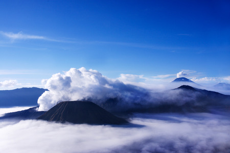 White smoke coming out of volcanoes surrounded by white clouds or fog and a clear blue sky seen at a distance in the afternoon from Mount Penanjakan, Indonesia.