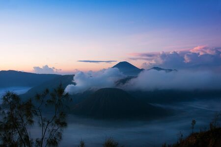 White smoke coming out of volcanoes surrounded by white clouds of mist and a clear blue sky seen at a distance in the morning from Mount Penanjakan at the Tengger Semeru National Park in East Java, Indonesia.