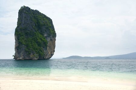 next horizon: Big high rock cliff filled with green vegetation surrounded by turquoise blue colored ocean water next to a tropical white sand beach with horizon view at midday, Krabi Thailand.