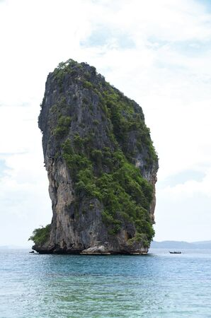Horizon view of a big high rock cliff filled with green vegetation surrounded by turquoise blue colored ocean water standing next to a small boat at midday, Krabi Thailand.