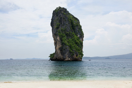 Big high rock cliff filled with green vegetation surrounded by turquoise blue colored ocean water next to a tropical white sand beach with horizon view at midday, Krabi Thailand.