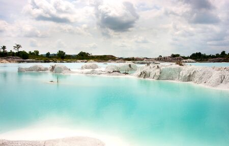 Man-made artificial lake Kaolin, turned from a mining ground holes. Land contains kaolinite and is white. Due to mining, holes were formed. and were covered by rain water, forming a clear blue lake, Air Raya Village, Tanjung Pandan, Belitung Island.