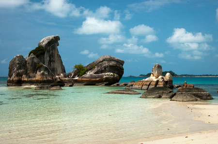 Natural rock formation in the sea and on a white sand beach in Belitung Island in the afternoon, Indonesia. Stock Photo