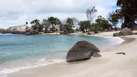 Natural rock formation on blue turquoise colored seashore and white sand beach with plants and trees at the background in Belitung Island in the afternoon, Indonesia. Imagens - 77674388