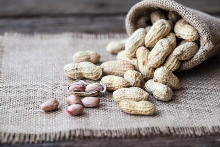 goober peas: Peanut in sacks on the wooden background