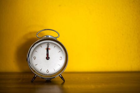Retro alarm clock on table with yellow wall background