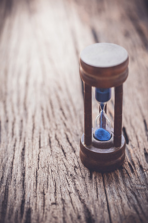 color tone: hourglass on wooden background,vintage color tone