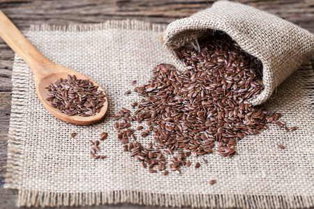Flax seeds in the sack on wooden background