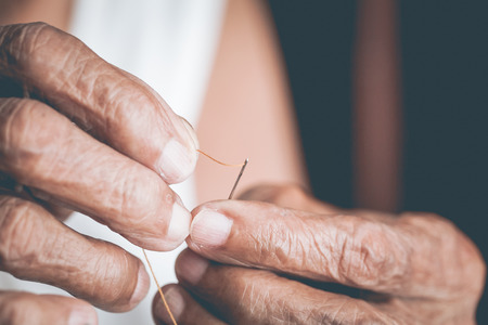 Old woman trying to thread a needle Stock Photo