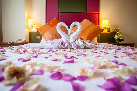 honeymoon suite: two swans made from towels with flower on honeymoon white bed