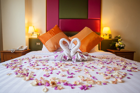 hotel bedroom: two swans made from towels with flower on honeymoon white bed