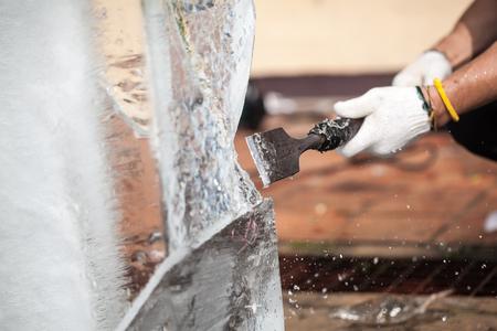 De man snijdt het ijsbeeld voor bruiloft Stockfoto