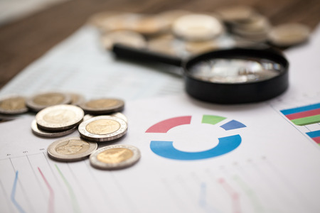 coins on bank account passbook and business chart Magnifying