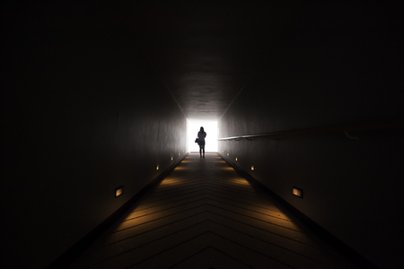 silhouette of a girl at the end of the tunnel