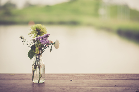 Beautiful Flowers In A Glass Vase On Wooden Table Stock Photo
