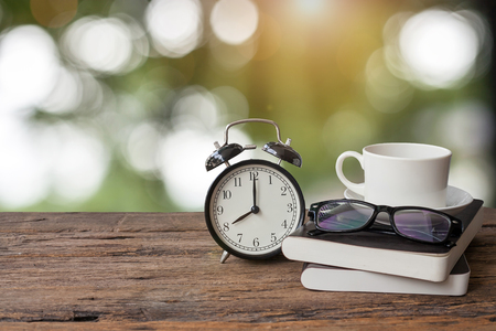 8 oclock retro clock, book, glasses and cup of coffee on wooden table