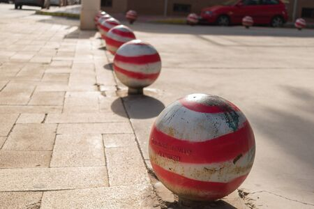 Red and white bollards on stone sidewalk Stock Photo