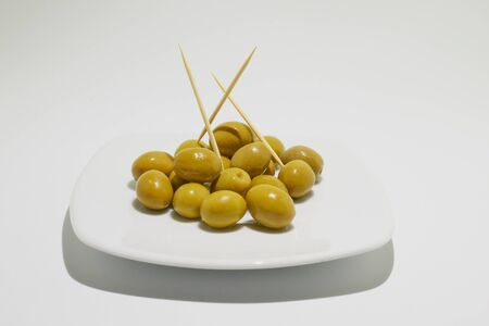 Green olives and chopsticks on plate with  white background Stock Photo