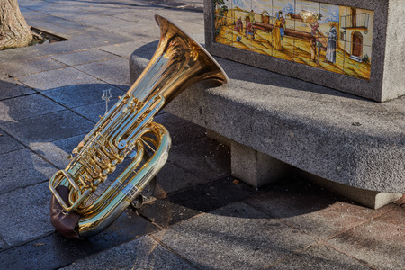 Close-up of a beautiful and bright tuba resting on a stone bench with ornament in Toledo, Spain