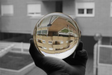 Close-up of the reflection of a building through a glass ball in black and white