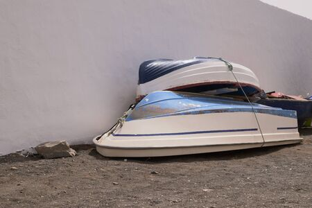 Two small boats saved after fishing next to a white wall in Fuerteventura, Spain Stock Photo