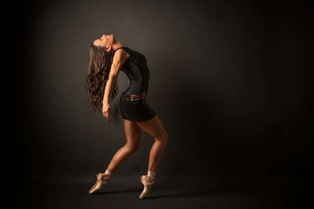 Dancer. Young elegant ballet dancer, dressed in black jersey, shoes and weightless black skirt is demonstrating ability to dance. Beautiful pose of classical ballet