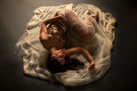 Ballerina. Young elegant ballet dancer, dressed in bright dress, ballet shoes and transparent veil lying on the floor. Beautiful pose of classical ballet
