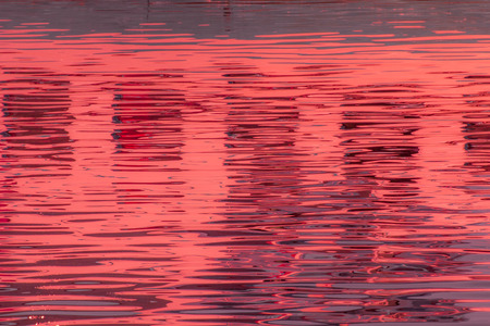 poetic: Reflection of windows in the waters of lake created by the light of the setting sun forming different size and shape of glimmer and colors Stock Photo