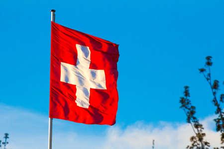 Swiss Confederation, Switzerland national flag waving on blue sky background Stock Photo