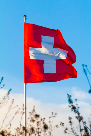 Constitución: Swiss Confederation, Switzerland national flag waving on blue sky background Foto de archivo