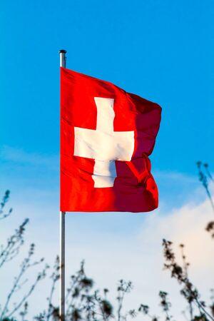 Swiss Confederation, Switzerland national flag waving on blue sky background Standard-Bild