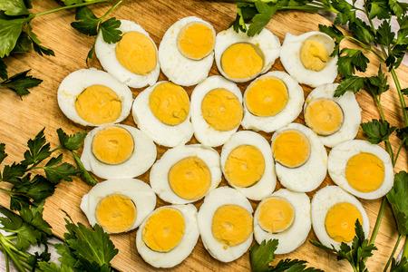 Huevos cocidos cortados en mitades decoradas con hojas frescas de perejil