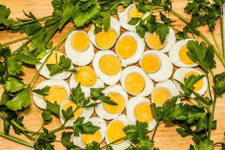 saturated: Boiled eggs cut in halves decorated with fresh parsley leaves Stock Photo