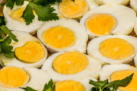 Boiled eggs cut in halves decorated with fresh parsley leaves Foto de archivo