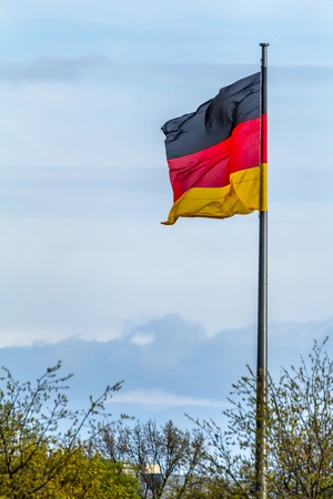 Federal Republic of Germany, German national flag waving on the blue sky background