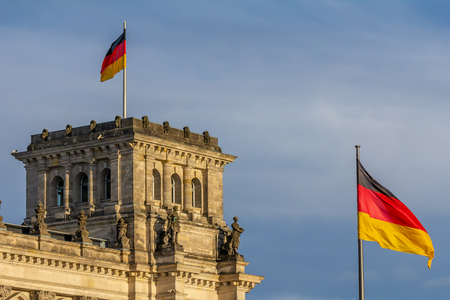 Federal Republic of Germany, German national flag at the Parliament building waving on the blue sky background 免版税图像