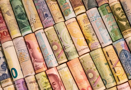 Different colourful banknotes from various countries on rolls to be used for illustrating subjects as business, banking, media, etc.