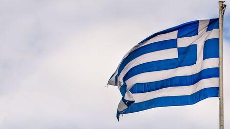 Greek national flag waving on blue sky background. Hellenic Republic, GR