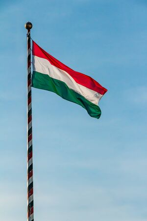Hungary, Hungarian national flag waving on blue sky background