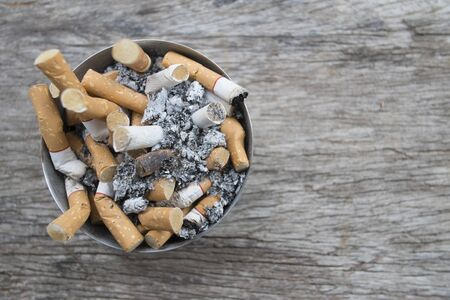 Ashtray full of cigarettes butts close-up on wood background