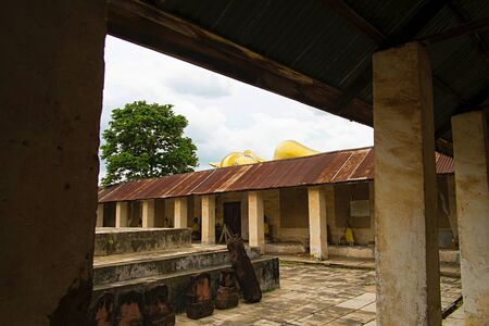In side of monastery old Thai Buddhist Temple with Face of Reclining Buddha behind zinc roof, Ratchaburi Thailand
