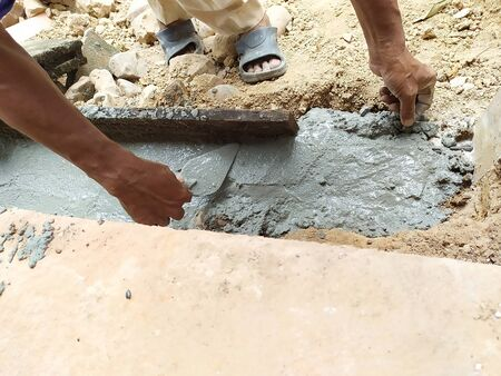 Worker use trowel to equalize cement, Construction and industrial concept Stok Fotoğraf