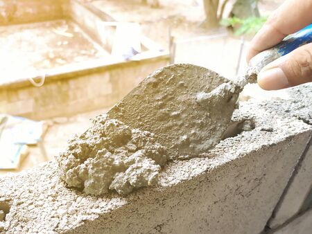 Bricklayer use trowel to make brick wall, close-up trowel, Construction and industrial concept