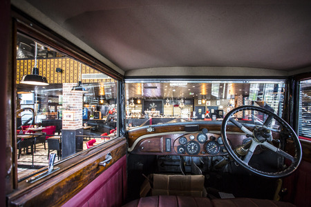 The vue of a well lit, picturesque and colourful dining area from inside a decorative vintage car 新聞圖片