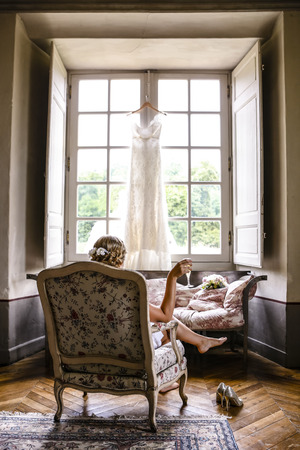 The bride contemplates with a glass of champagne and observes her suspended wedding dress before the big ceremony. Banco de Imagens