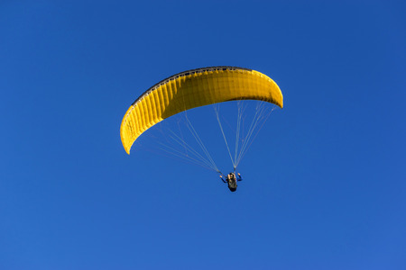 Yellow paraglider flying across a blue Sky
