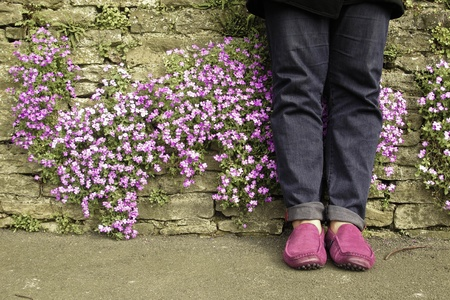 small purple flower: Guy foot lean against the wall with small purple flower Stock Photo