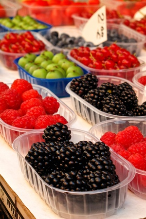 A selection of berries and fruit in a rainbow of colors at an outdoor market stall