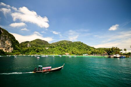 Motor boat in the sea with mountain background ans blue sky, Thailand Stock Photo - 13703761